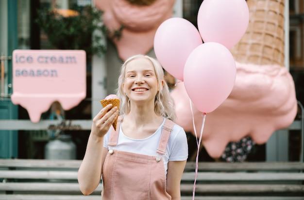 Portrait d'une jolie dame marchant dans la rue avec de la crème glacée et des ballons
