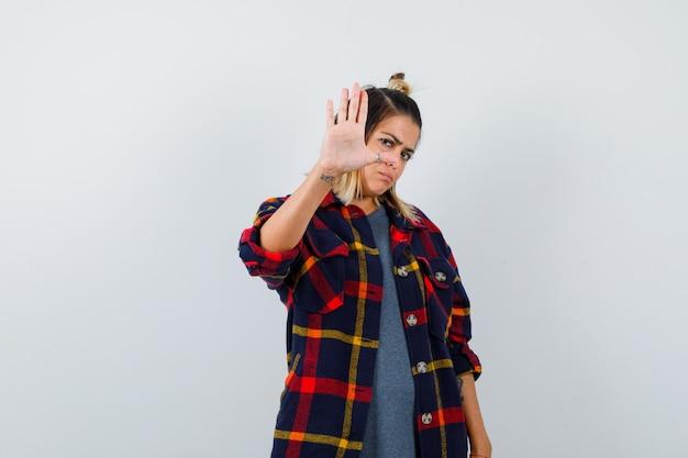 Portrait de jolie dame montrant un geste de refus en chemise décontractée et à la vue de face agacée