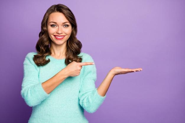 Portrait de jolie dame ondulée tenir le bras ouvert conseillant le produit de nouveauté indiquant le doigt cool bas prix porter un pull duveteux sarcelle décontracté.