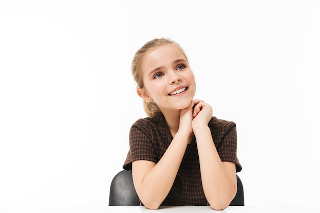 Portrait d'une jolie écolière assise au bureau pendant une leçon tout en étudiant des matières à l'école isolée sur un mur blanc