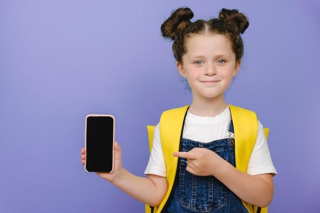 Portrait d'une jolie écolière attrayante et gaie démontrant une annonce d'affichage de gadget offre une application de service web 5g, porte un sac à dos jaune, isolée sur un fond de couleur pastel violet en studio