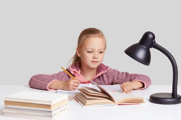 Portrait d'une jolie écolière aux cheveux clairs regarde attentivement le livre, écrit des informations avec un crayon dans le bloc-notes, fait ses devoirs, pose contre le mur blanc, liseuse sur le bureau. enfants, apprentissage