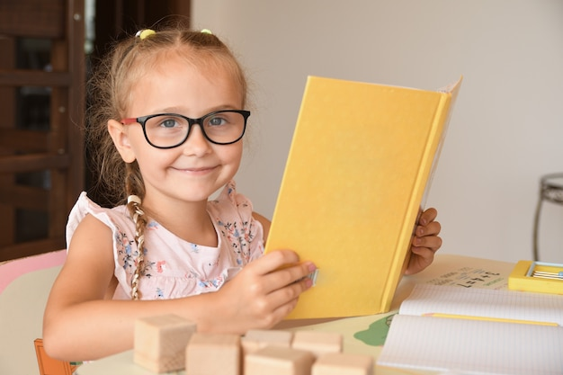 Portrait de jolie élève de maternelle assis dans la salle de classe tout en lisant des manuels.petite fille assise à un bureau et lisant un livre.