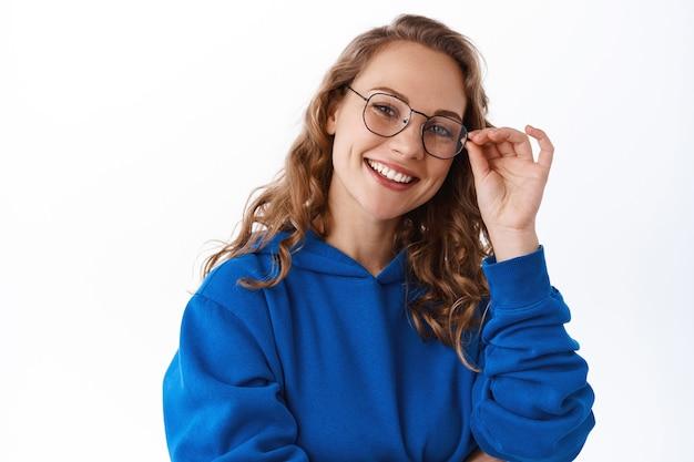 Portrait d'une jolie étudiante blonde, portant des lunettes et souriante déterminée, l'air intelligente, debout sur un mur blanc
