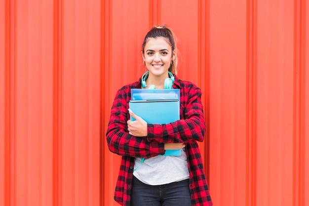 Portrait de jolie étudiante dans smart casual tenue des livres en main debout contre le mur à la recherche d'appareil photo