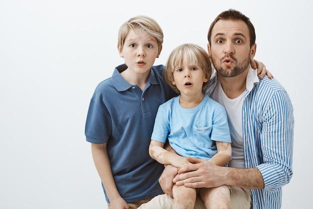Portrait de jolie famille de fils et père, étreindre et debout surpris
