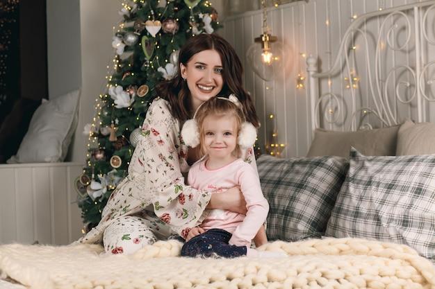Portrait de jolie famille heureuse en pyjama à noël au lit