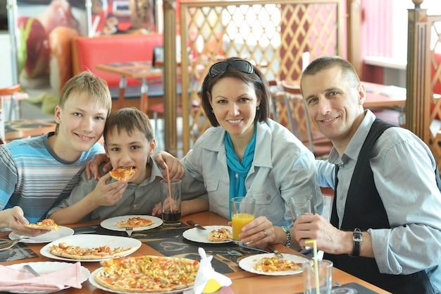 Portrait d'une jolie famille mangeant de la pizza au café