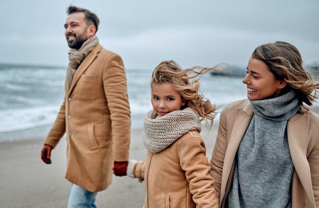 Portrait d'une jolie famille marchant, main dans la main sur la plage en hiver.
