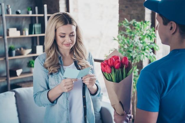 Portrait de jolie femme adorable lire la carte recevoir des fleurs rouges