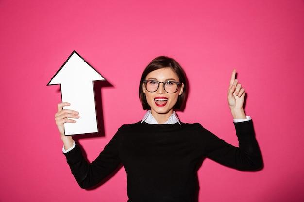 Portrait d'une jolie femme d'affaires heureuse avec flèche pointant vers le haut