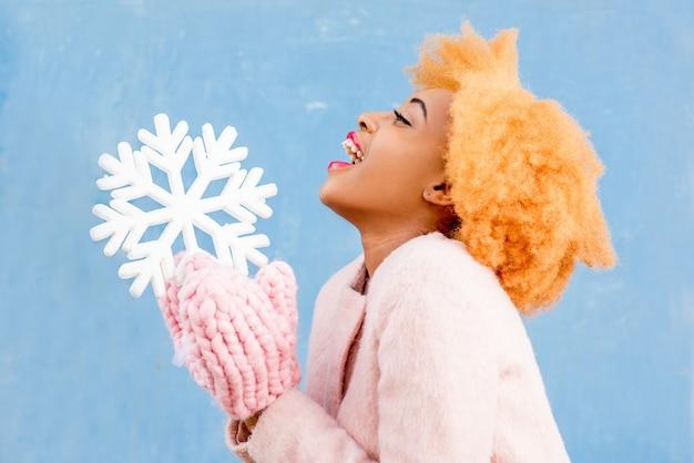 Portrait d'une jolie femme africaine au manteau rose tenant un flocon de neige artificiel sur fond de mur bleu. concept de saison d'hiver