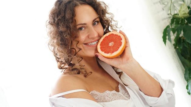 Portrait de jolie femme d'âge moyen aux cheveux bouclés avec pamplemousse à la maison - fond blanc. le concept de bonheur, de beauté et de santé