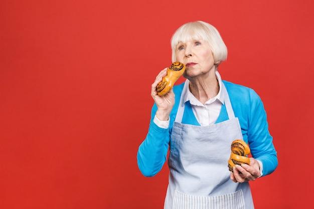 Portrait de jolie femme âgée gaie assez charmante avec rides montrant gesticulant douce boulangerie maison