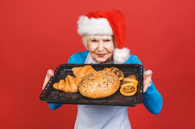 Portrait de jolie femme âgée gaie avec des rides montrant des gestes des produits de boulangerie sucrés faits maison