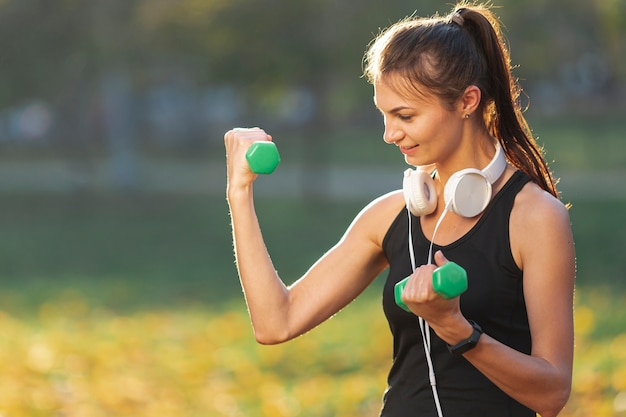 Portrait de jolie femme à l'aide de poids de fitness