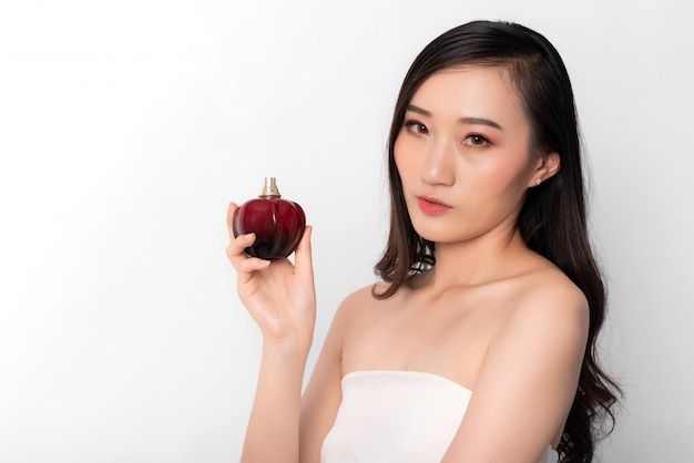 Portrait de jolie femme asiatique à la mode posant avec une bouteille de parfum