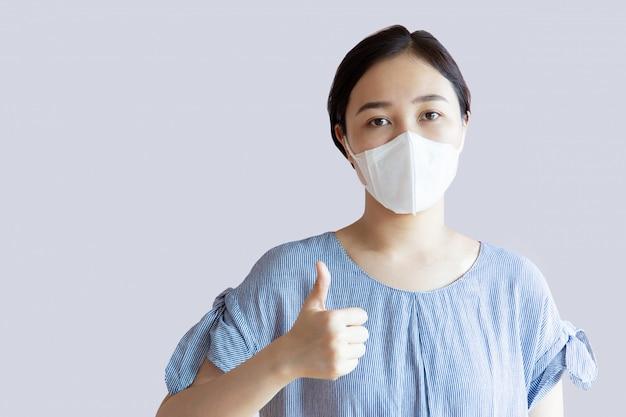 Portrait de jolie femme asiatique portant un masque facial d'hygiène se bouchent.