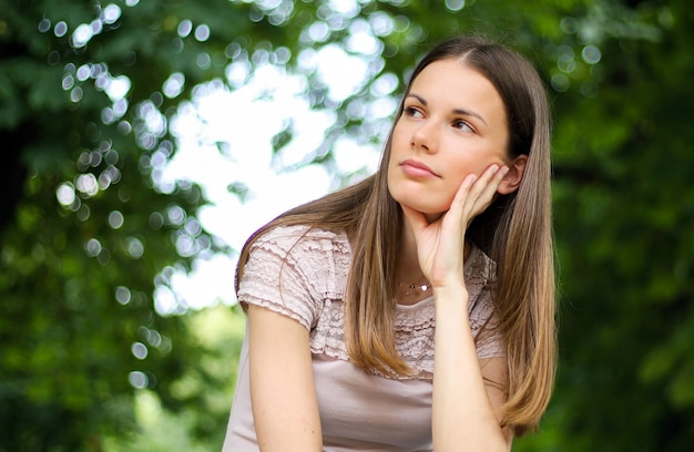 Portrait d'une jolie femme assise sur un banc dans un parc