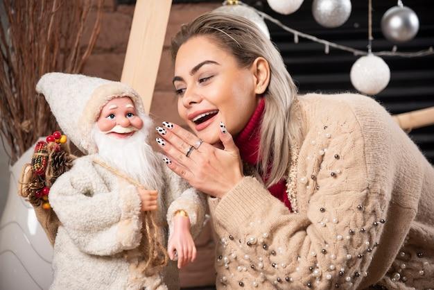 Portrait de jolie femme assise avec jouet père noël photo de haute qualité