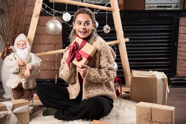 Portrait de jolie femme assise et tenant un cadeau de noël
