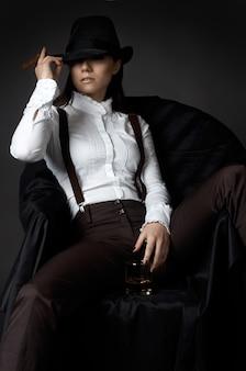 Portrait de jolie femme au chapeau fumer cigarette