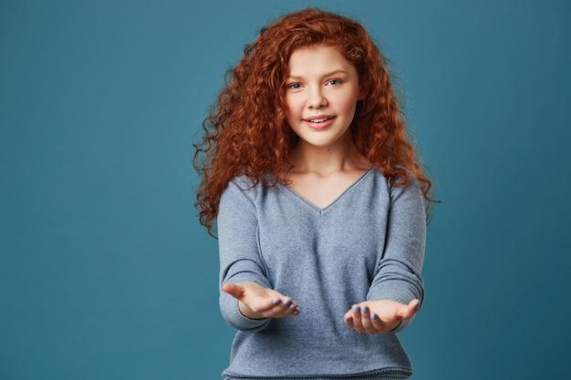 Portrait de jolie femme aux cheveux roux ondulés et taches de rousseur en chemise grise avec une expression heureuse et détendue.