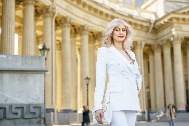 Portrait d'une jolie femme blonde dans une veste blanche dans la rue par une journée ensoleillée