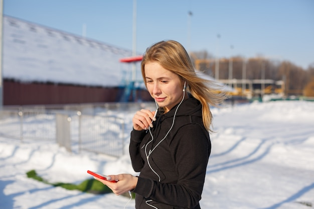 Portrait d'une jolie femme blonde, écouter de la musique tout en marchant dans la rue, tenant un téléphone rouge à la main. la neige se trouve autour.