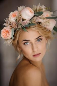 Portrait de la jolie femme blonde seins nus dans une couronne florale tendre