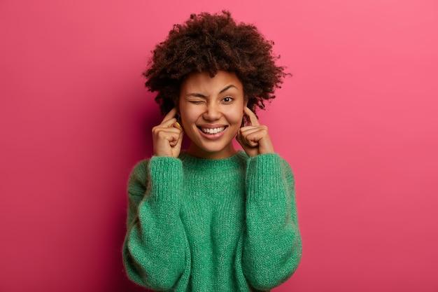 Portrait de jolie femme bouche les oreilles et cligne des yeux, sourit largement, ignore les bruits désagréables, porte un pull vert, pose contre le mur rose, a une expression heureuse. éteignez le volume.
