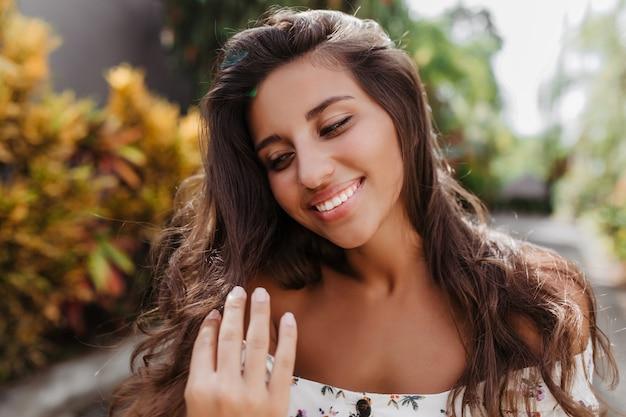 Portrait de jolie femme bronzée aux longs cheveux bouclés souriant contre le mur d'arbres