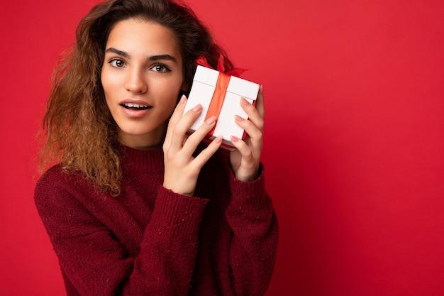 Portrait d'une jolie femme brune adulte étonnée réfléchie heureuse et bouclée isolée sur rouge