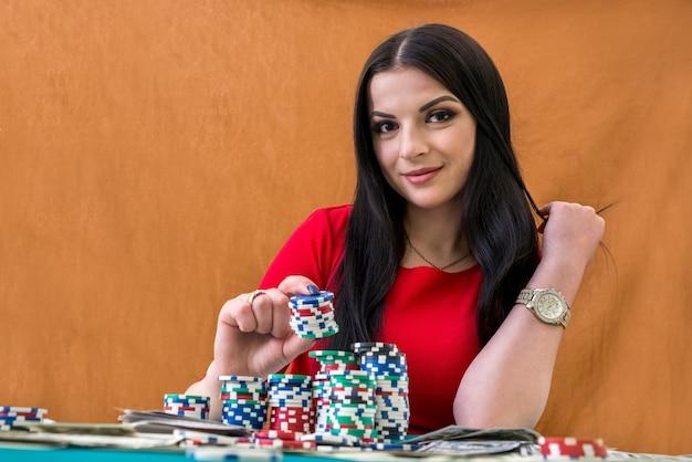 Portrait de jolie femme brune avec des jetons de casino