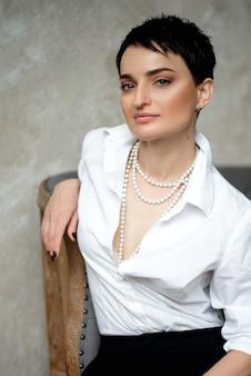 Portrait de jolie femme brune portant chemise blanche et collier de perles.