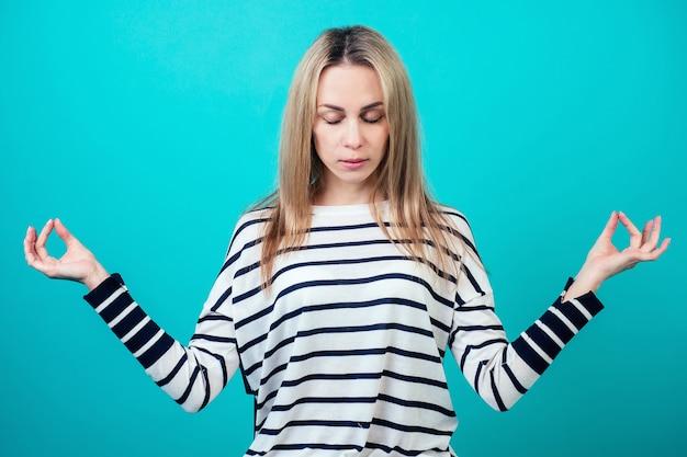 Portrait d'une jolie femme calme aux cheveux blonds courts et au maquillage médite et pratique le yoga en studio sur fond bleu.