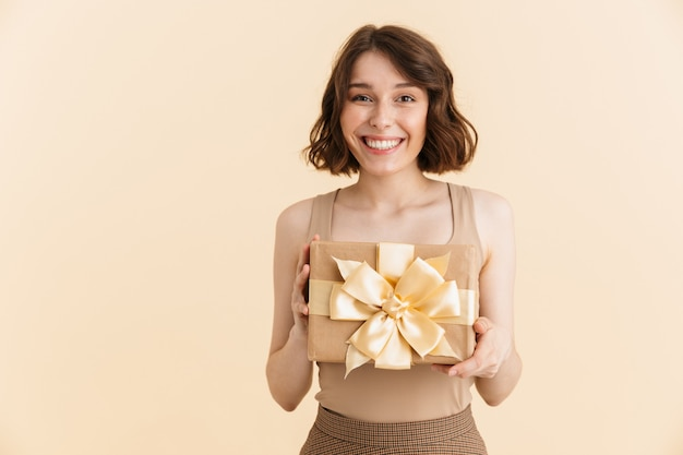 Portrait d'une jolie femme caucasienne des années 20 vêtue de vêtements décontractés souriant tout en tenant une boîte présente isolée