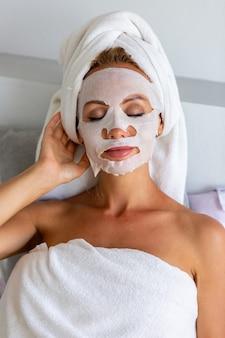 Portrait de jolie femme caucasienne calme avec une serviette sur la tête et un masque