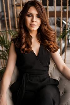 Portrait d'une jolie femme sur une chaise confortable pour le repos chambre loft avec plante verte