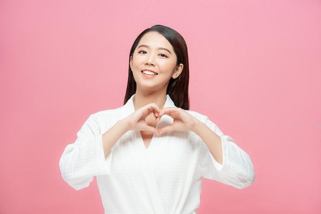 Portrait d'une jolie femme en chemise à carreaux elle fait en forme de coeur par ses mains debout sur fond rose et regardant la caméra