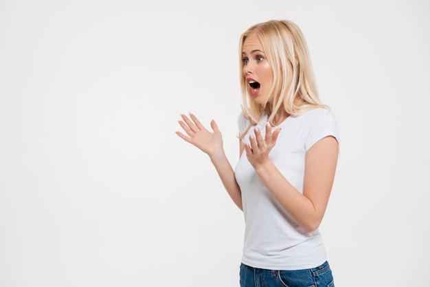 Portrait d'une jolie femme choquée, gesticulant avec les mains
