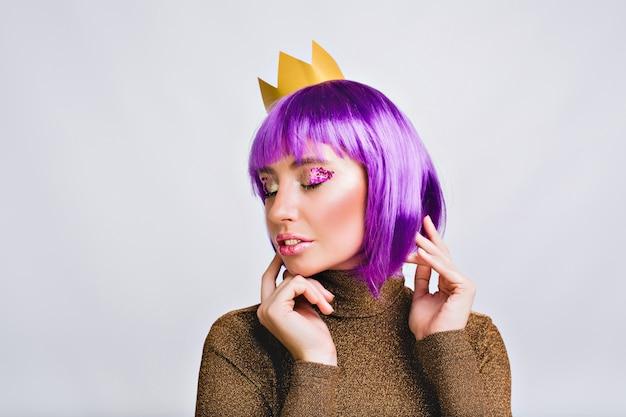 Portrait jolie femme avec une coiffure violette en couronne d'or. elle a l'air paisible, a des guirlandes violettes sur les yeux fermés.
