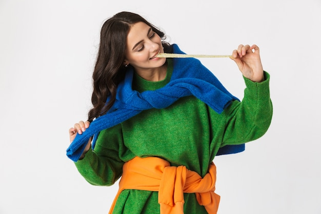 Portrait de jolie femme dans des vêtements colorés à mâcher de la gomme longue, debout isolé sur blanc