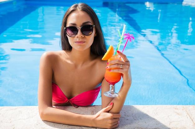 Portrait d'une jolie femme debout dans la piscine et tenant un cocktail à l'extérieur