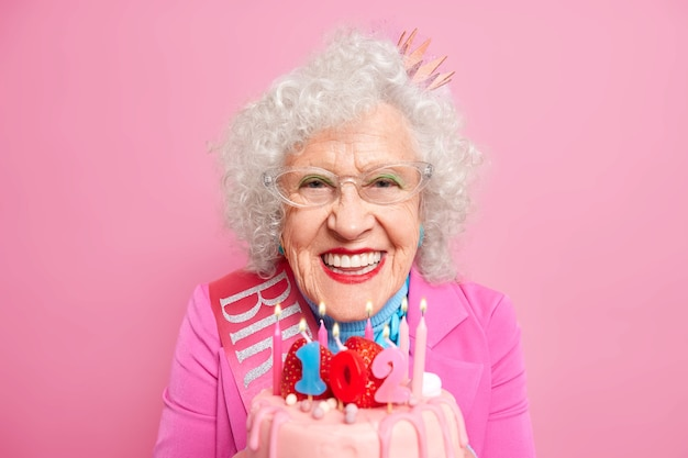 Portrait d'une jolie femme avec du maquillage célèbre son 102e anniversaire souffle des bougies sur un gâteau d'anniversaire sourit avec plaisir porte des vêtements de fête a la fête