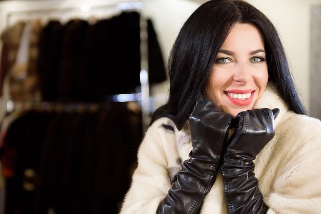 Portrait de jolie femme élégante en fourrure dans un magasin.