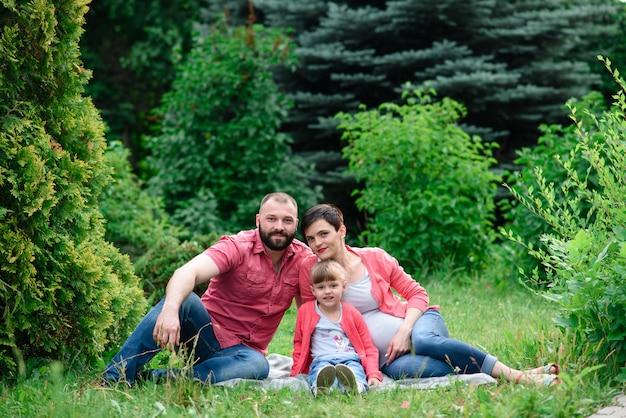 Portrait de jolie femme enceinte avec son jeune mari et son petit enfant mignon embrassant et marchant dans le parc.