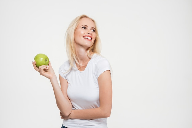 Portrait d'une jolie femme heureuse tenant une pomme verte