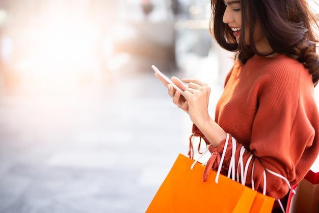 Portrait d'une jolie femme heureuse tenant des sacs à provisions tout en utilisant un smartphone