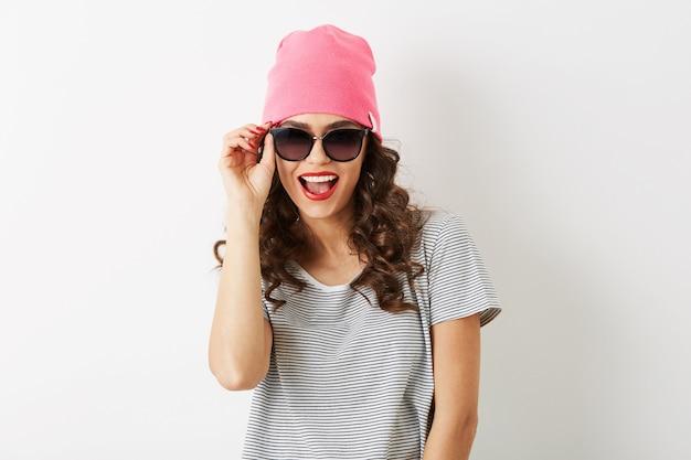 Portrait de jolie femme hipster avec expression de visage drôle sorti, émotionnel, en chapeau rose, lunettes de soleil, souriant, bonne humeur, isolé, dents blanches, lèvres rouges, cheveux bouclés